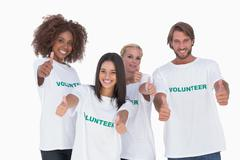 Happy group of volunteers giving thumbs up - stock photo