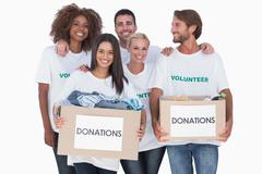 Stock Photo of Happy group of volunteers holding clothes donation boxes