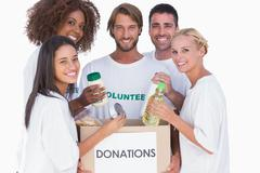 Stock Photo of Happy volunteers putting food in donation box