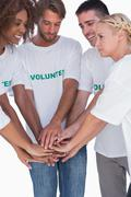 Stock Photo of Smiling volunteers putting hands together