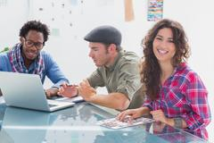 Stock Photo of Creative team working together with one smiling at camera
