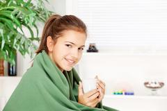 Woman under blanket drinking tea Stock Photos