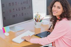 Editor using graphics tablet to do work and smiling at camera - stock photo