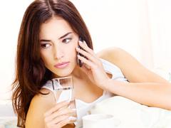 Glass of water and phone in bed Stock Photos