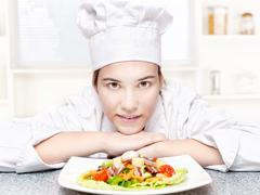 Pretty young chef and hers plate of a delicious salad in kitchen Stock Photos