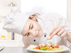 Young chef decorating delicious salad Stock Photos