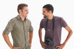 Stock Photo of Stylish friends smiling at each other with one holding camera