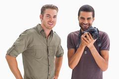 Stock Photo of Stylish friends smiling with one holding camera