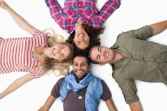 Stock Photo of Friends lying in a circle and smiling at camera