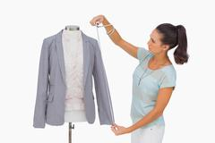 Fashion designer measuring blazer sleeve on mannequin Stock Photos
