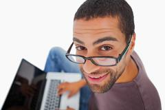 Man wearing glasses sitting on floor using laptop and smiling up at camera - stock photo