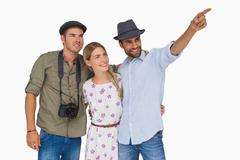 Stock Photo of Man pointing to something with friends and one has camera