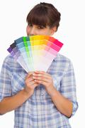 Pretty woman with fringe showing colour charts - stock photo