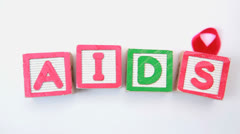 Aids spelled out in blocks with red ribbon - stock footage