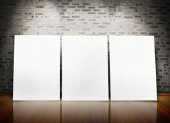 Three posters standing in line in a parquet floor like an art exhibition - stock photo