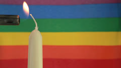 Candle lit against rainbow flag Stock Footage