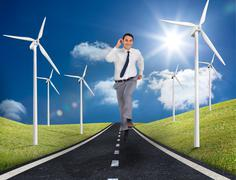 Businessman running on a road next to windmills - stock photo