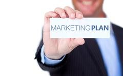 Stock Photo of Businessman holding a label with marketing plan written on it