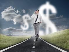 Stock Photo of Dollar currency behind businessman running on a road