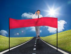 Stock Photo of Smiling young businessman running on a road with copy space banner