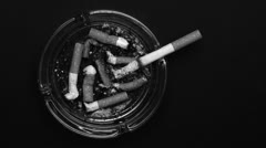 Cigarette burning in ashtray and being put out - stock footage