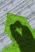 Shadows of embracing couple on wooden boards representing a house - stock photo