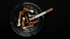 Cigarette burning in ashtray Stock Footage