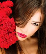 Woman and bouquet of red carnations Stock Photos