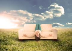 Woman sitting upside down on couch in field - stock photo