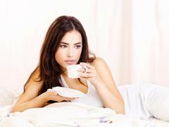 Pretty woman dink coffee in bed Stock Photos