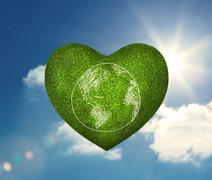 Green heart shape with earth drawn on it - stock photo