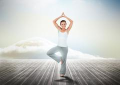 Woman practicing yoga over wooden boards - stock photo
