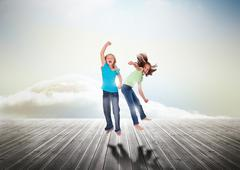 Sisters having fun jumping over wooden boards Stock Photos