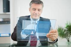 Businessman using futuristic touchscreen to view social network profile - stock photo