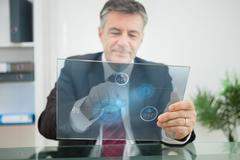 Stock Photo of Businessman using futuristic touchscreen to view statistics