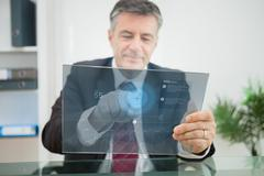 Businessman using futuristic touchscreen to view data - stock photo