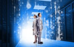 Business people standing back to back in data center - stock photo