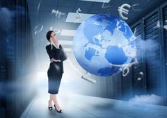 Businesswoman standing in data center with earth and currency graphics Stock Photos