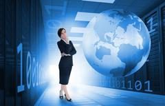 Businesswoman standing in data center with earth and binary code graphics - stock photo