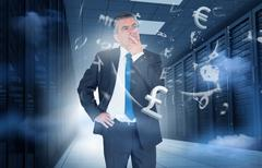 Stock Photo of Businessman standing in data center with currency graphics