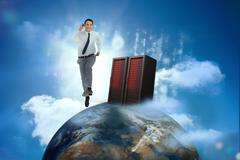 Stock Photo of Businessman racing on top of the world beside server