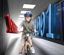 Happy boy on a bike in data center - stock photo