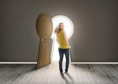 Woman walking towards keyhole shaped doorway with light Stock Photos
