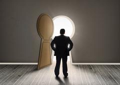 Buisnessman looking at keyhole shape door revealing light - stock photo