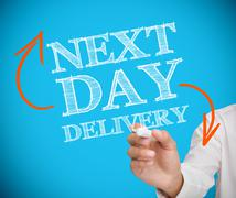 Businessman writing next day delivery - stock photo