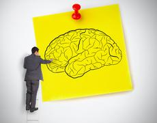 Businessman drawing a brain on a giant post it Stock Photos
