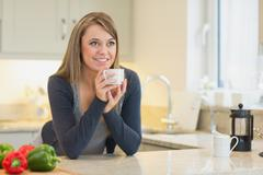 Stock Photo of Woman in the kitchen drinking hot beverage