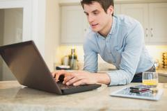 Enthusiastic man surfing the internet - stock photo