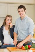 Pregnant woman eating vegetables prepared by husband Stock Photos