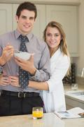 Stock Photo of Man eating cereal while his wife is hugging him
